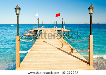 light poles and rope fence on wooden pier - stock photo