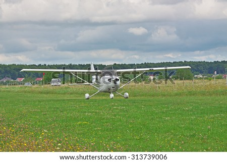 Light private plane taking off from the ground airstrip on a stormy day - stock photo