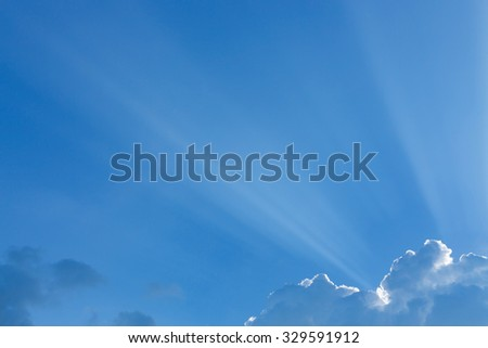 light rays of sun beam through clouds in clear blue sky background