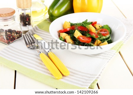 Light salad in plate on wooden table - stock photo