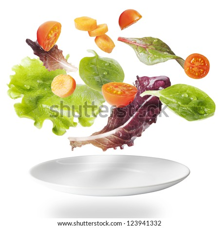 Light salad with floating vegetables. Vegetables in suspension - stock photo