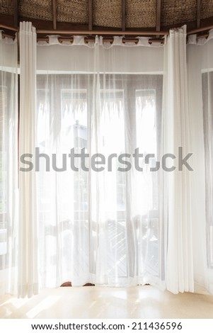 Light shines through white curtains in room - stock photo