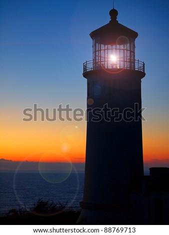 Light Shining in the North Head Lighthouse on the Washington Coast at Sunset - stock photo