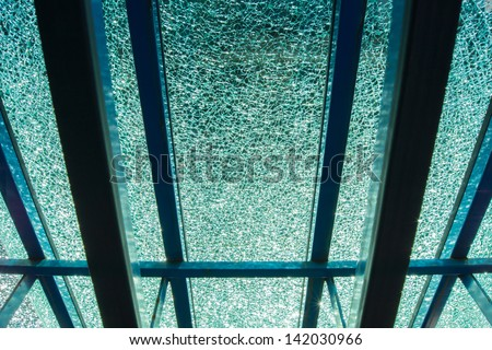 Light shining through a piece of broken tempered glass leaning against an easel - stock photo