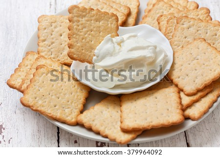 light snack of crackers and cream cheese on blue napkin on - stock photo