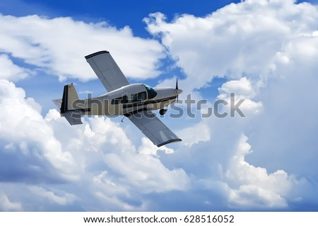 Light-sport aircraft on blue sky background with white clouds