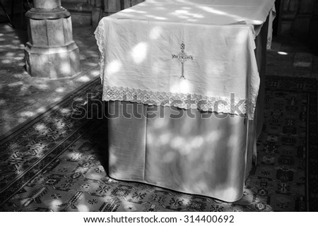 Light spots on the altar and the floor in church. Sunlight filtered through the stained glass window. A game of light and shadow. Aged photo. Black and white. - stock photo