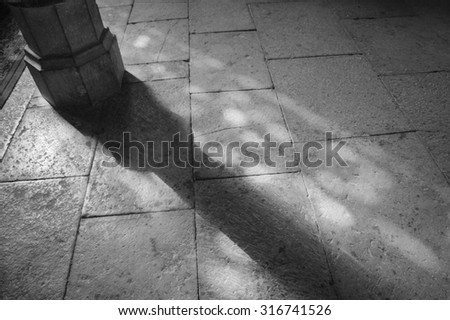 Light spots on the the floor in church. Sunlight filtered through the stained glass window. A game of light and shadow. Aged photo. Black and white. - stock photo