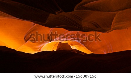Light streams down the orange sandstone walls of a canyon in Arizona.  - stock photo