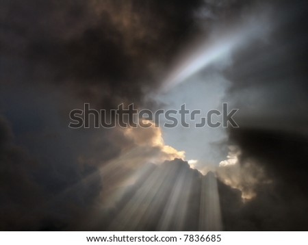 Light streams out from stormy clouds - stock photo