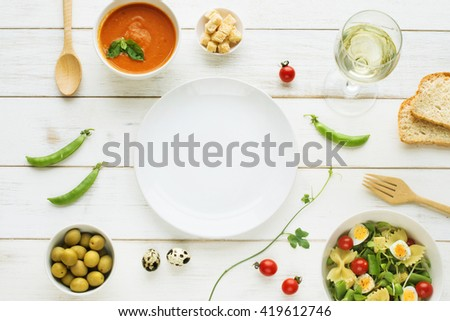 Light summer dinner / supper concept. Green salad with pasta, cherry tomato, quail eggs. Cold tomato soup (gazpacho) with croutons, green olives, fresh bread and glass of cold white wine.  - stock photo