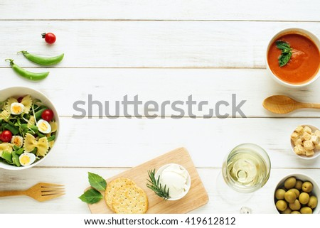 Light summer dinner / supper concept. Green salad with pasta, cherry tomato, quail eggs. Cold tomato soup (gazpacho), croutons, green olives, crackers and glass of cold white wine.  - stock photo