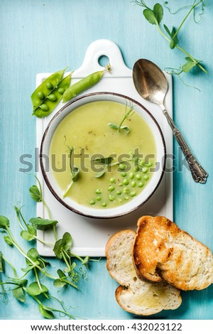 Light summer green pea cream soup in bowl with sprouts, bread toasts and spices. White ceramic board in the center, turquoise blue wooden background. Top view - stock photo