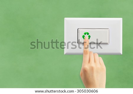 Light switch and hand on a green wall background, ecology concept - stock photo
