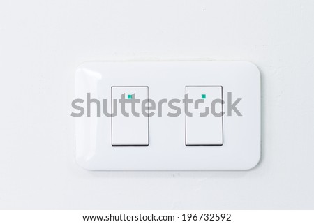 light switch on white wall - stock photo