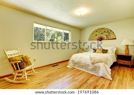 Light tones bedroom with hardwood floor, bed and rocking chair. Room decorated with asian style elements