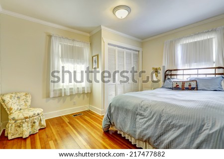 Light tones bedroom with hardwood floor. Furnished with iron frame bed and floral chair
