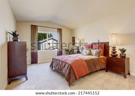 Light tones bedroom with vaulted ceiling. Beautiful mocha and orange bedding. - stock photo