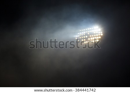 Light tower lit at a stadium during nightime. - stock photo