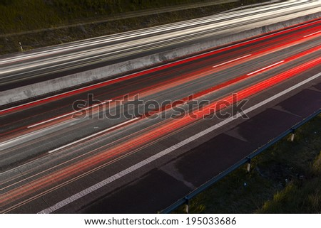 Light trails at night on a highway light bands freeway - stock photo