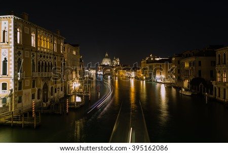 Light trails from boats on the Grand Canal in Venice with Basilica di Santa Maria della Salute in the background
