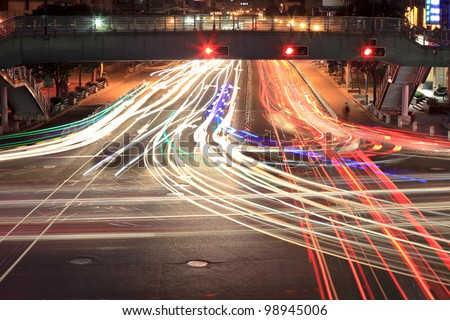 light trails on crossroad in rush hour traffic at night - stock photo