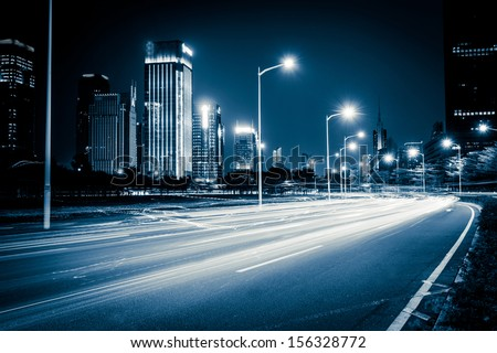 light trails on the modern city street at night - stock photo