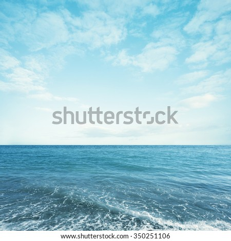Light turquoise sea water with sky and fluffy clouds. Summer seascape - stock photo