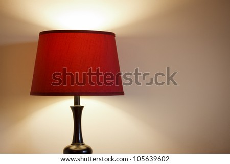 Light with red lamp shade creating nice light and shadows on wall. - stock photo