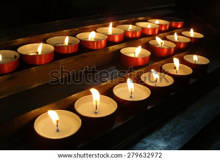 lighted candles in the church above the altar  - stock photo