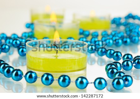 Lighted candles with beads close up - stock photo