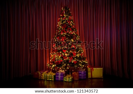 lighted Christmas tree with presents - stock photo
