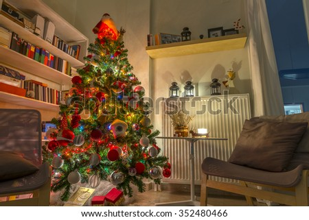 Lighted Christmas tree with presents underneath in a modern living room.