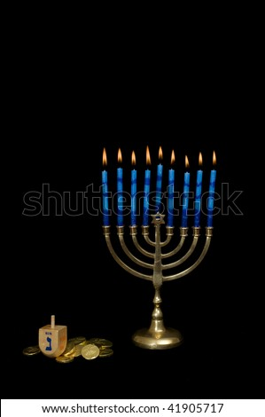 Lighted Menorah with Hanukkah gelt and dreidel at the base set on a black background.