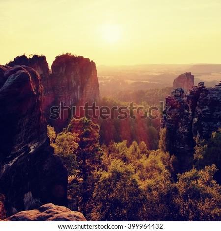 lighted rocks and hills bellow sunset sun on  horizon. Dark forest - stock photo