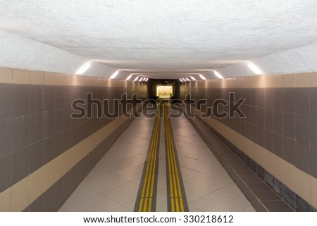 lighted underground passage under the highway, with a low ceiling - stock photo
