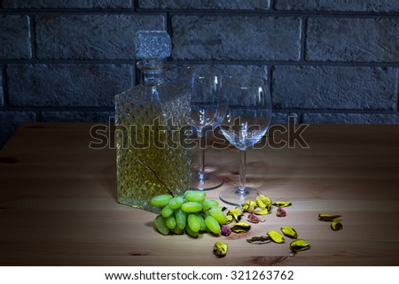 Lightened crystal carafe of white wine, two glass, grapes on wooden table and gray bricks background  - stock photo