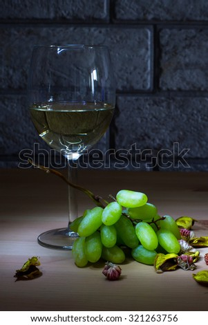 Lightened glass of white wine and grapes on wooden table and gray bricks background - stock photo