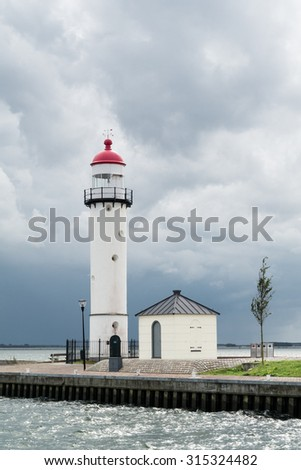 Lighthouse against dark sky of storm clouds in Hellevoetsluis on the island Voorne Putten, South Holland, Netherlands