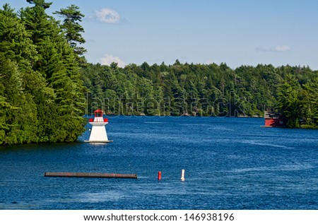 Lighthouse and a boathouse - stock photo