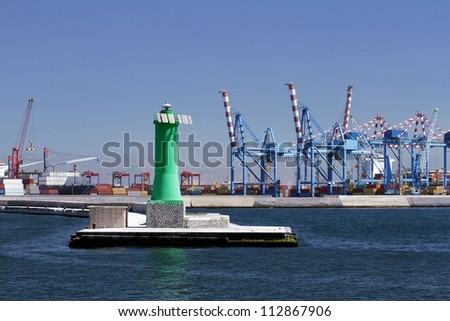 Lighthouse and cranes in port