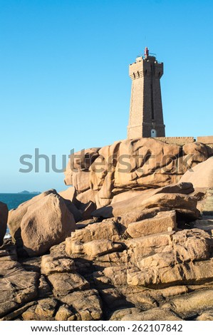 Lighthouse and iconic shaped rocks on the Pink Granite Coast in Brittany in the northwest part of France. - stock photo