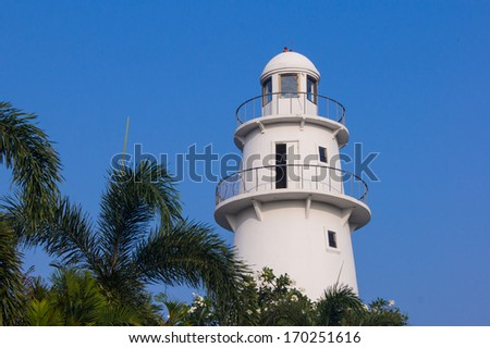 lighthouse and palm tree with sky blue - stock photo