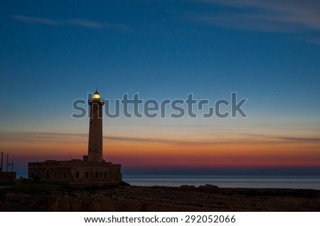 Lighthouse and starry night before the sunrise