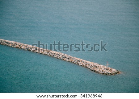 Lighthouse at horizon of breakwater. - stock photo