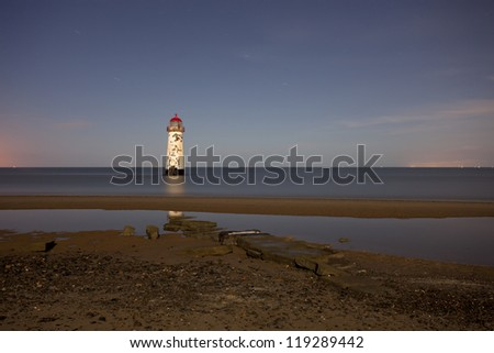 lighthouse at night under the full moon - stock photo