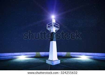 Lighthouse at starry night with searchlight beam - stock photo