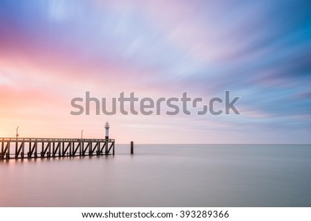 Lighthouse at the end of a pier during sunset - stock photo