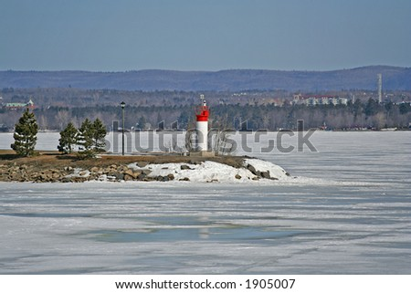 Lighthouse at the frozen river - stock photo