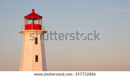 Lighthouse detail and sky in early morning sunlight. - stock photo